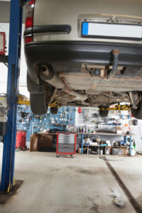 Car under repair on service lift in garage