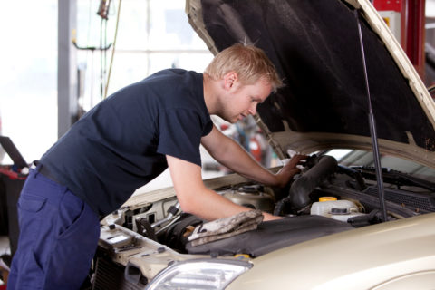A young mechanic under the hood of a car doing repairs
